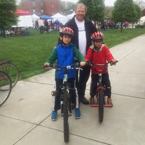 Attorney David White with children sitting on bicycles, wearing bicycle helmets