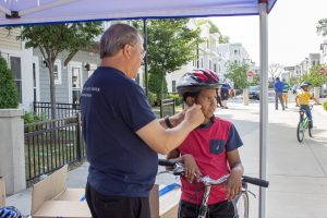A boy receiving a new bicycle helmet.