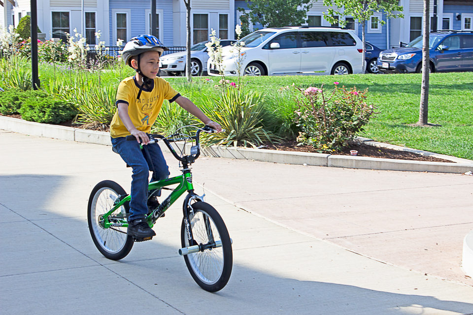 A child riding a bicycle wearing a bicycle helmet.