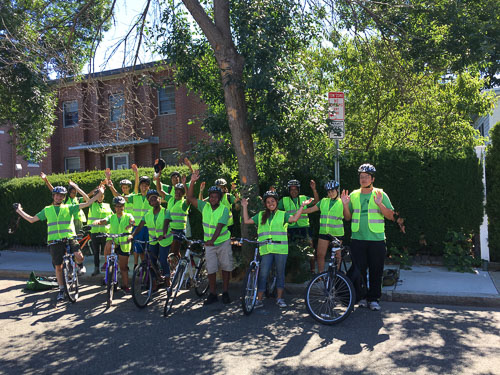 Students wearing bicycle helmets and neon vests in Somerville, Massachusetts.