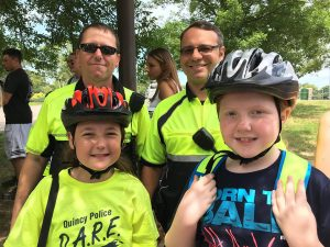 Quincy police officers and kids wearing bike helmets