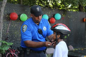 Cambridge police officer fitting bike helmets