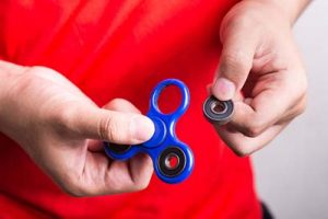 Fidget spinner missing a piece in boy's hands