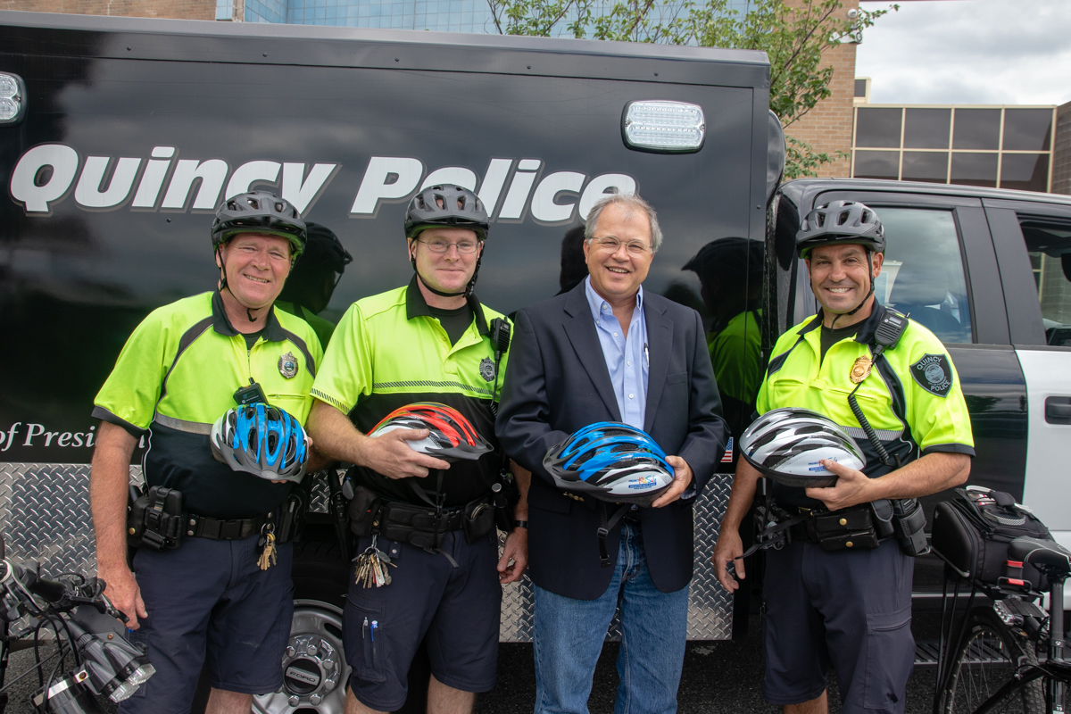 Quincy, MA police officers with kids' bicycle helmets donated by Boston law firm