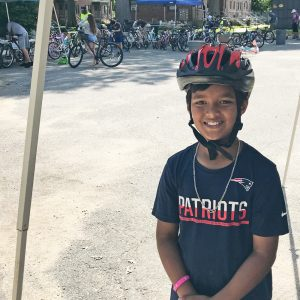 child in Arlington wearing a bike helmet donated by Breakstone, White & Gluck's Project KidSafe campaign