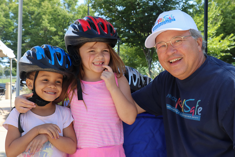 Attorney David W. White fitting bicycle helmets for kids at the Tierney Learning Center in South Boston.