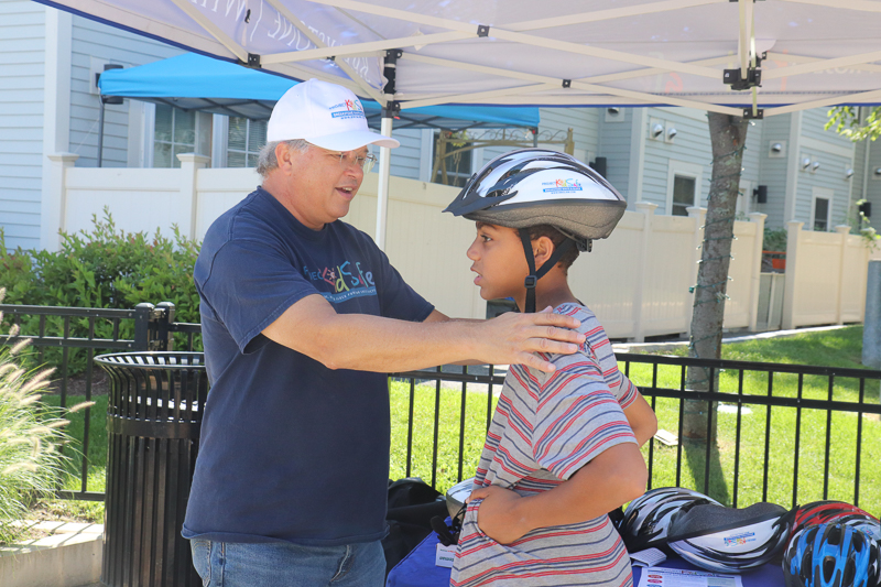Attorney David W. White fits a helmet for a teenager at the Tierney Learning Center.