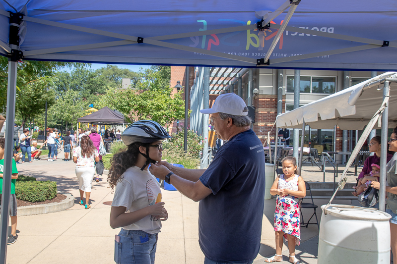 Attorney David W. White fits a bicycle helmet for a young girl at the Tierney Learning Center in South Boston.
