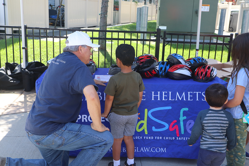 Attorney David W. White helping a young cyclist select a bicycle helmet.