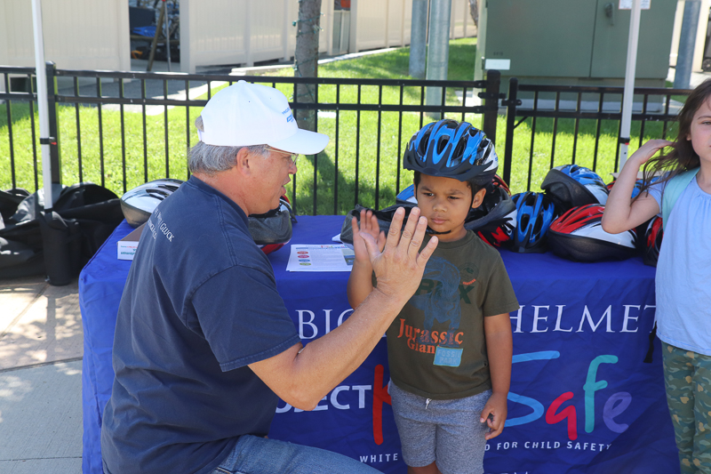 High five after Attorney David W. White fits a helmet for a young cyclist. Breakstone, White & Gluck donated the bicycle helmets to the Tierney Learning Center's Back to School BBQ.