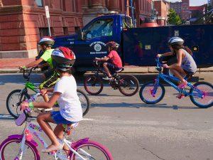 Kids riding bikes wearing Project KidSafe bike helmets in Lawrence, Massachusetts