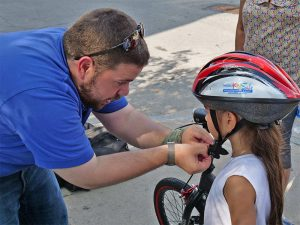 Man fitting Project KidSafe bicycle helmet for young girl in Lawrence, Massachusetts