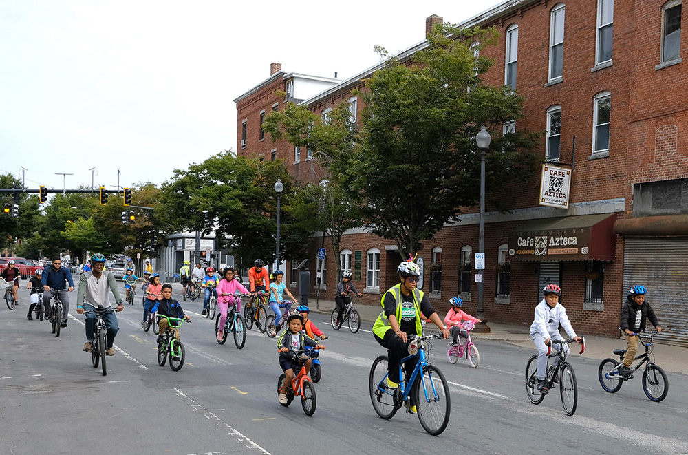 Cyclists riding and wearing bicycle helmets at the Lawrence Ciclovia. Breakstone, White & Gluck, a Boston personal injury law firm, donated helmets from its Project KidSafe campaign.
