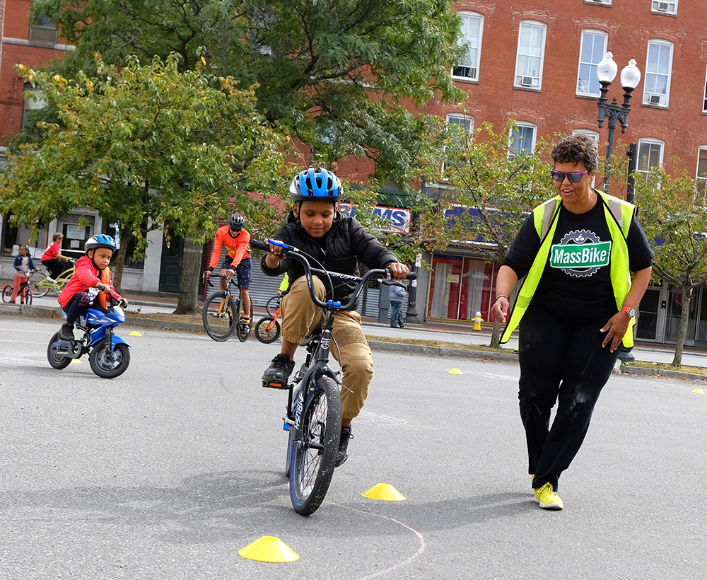 Child riding around obstacle course at the Lawrence Ciclovia. Breakstone, White & Gluck, a Boston personal injury law firm, donated bicycle helmets for the kids.