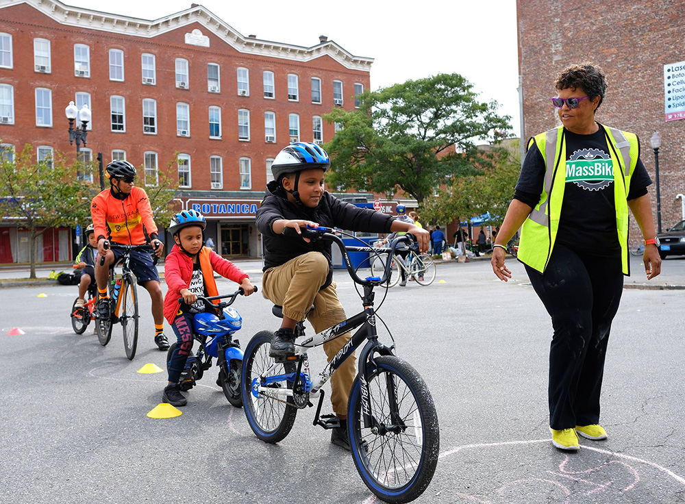 Children wearing Project KidSafe bicycle helmets at the Lawrence Ciclovia this summer. Breakstone, White & Gluck, a Boston personal injury law firm, donated the helmets as part of its Project KidSafe campaign.