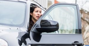 Woman with SUV door open, putting cyclists at risk for dooring injuries.