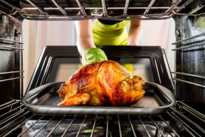 Woman putting Thanksgiving turkey in oven
