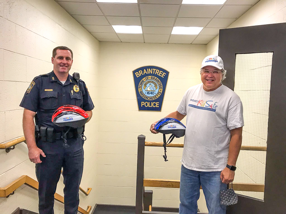 Boston lawyers of Breakstone, White & Gluck give Braintree Police free bike helmets for children.