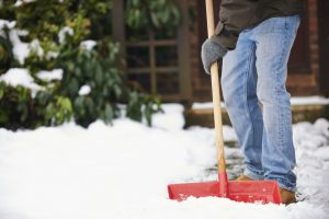 Man Clearing Snow From Path With Shovel
