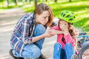 Mother helps daughter after a minor fall off a bicycle.