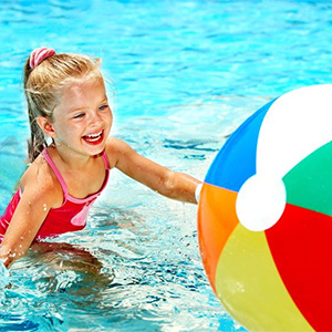 Young girl playing in a swimming pool with a beach ball.