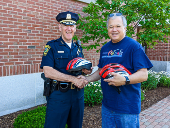 Norwood Police Chief receives children's bicycle helmets to help promote bike safety.