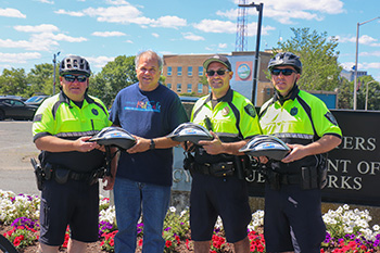 Quincy Police officers receive free bicycle helmets for children from Breakstone, White & Gluck of Boston.