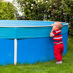 Young child at risk for falling and drowning in a backyard swimming pool.