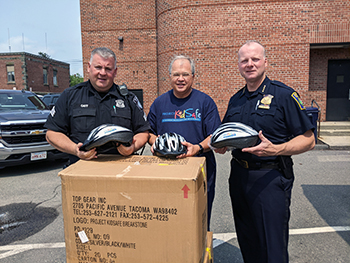 Breakstone, White & Gluck makes a donation of children's bicycle helmets to the Everett Police Department.