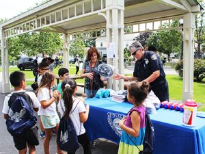 Waltham Police officer gives away free children's bicycle helmets donated by Boston law firm of Breakstone, White & Gluck